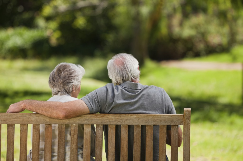 An elderly couple sat on a park bench