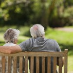 An elderly couple sat on a park bench
